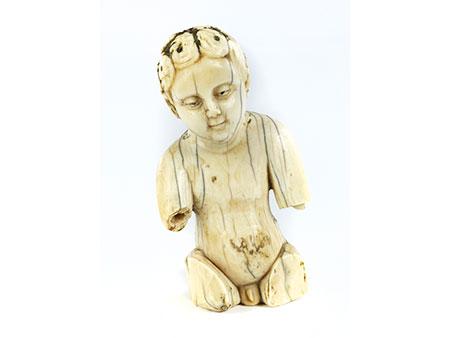 Kleine Elfenbeinfigur eines sitzenden Knäbleins