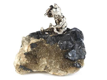 Schlägelnder silberner Zwerg auf Gesteinsstufe