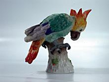 Porzellanfigur eines buntbemalten Kakadu auf Holzstamm