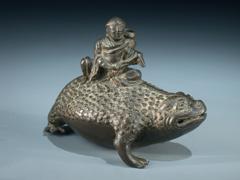Bronze-Darstellung einer Kröte mit darauf sitzendem Einsiedler.