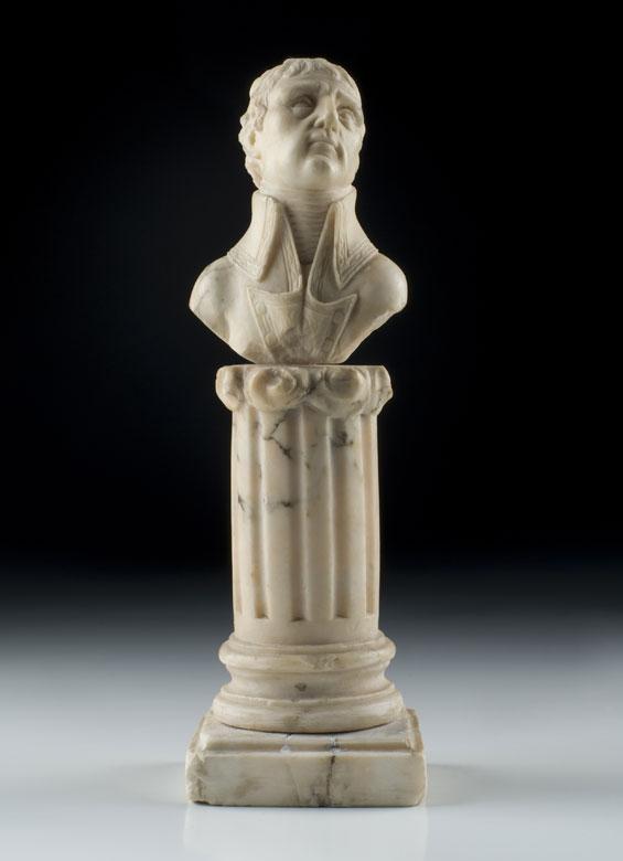 Kleine Marmorbüste eines Adeligen oder Feldherrn Höhe: 18 cm. Um 1800. Auf einem kannelierten Säulenstumpf. Die Oberseite des Stumpfes mit Wolken umgeben. Rundbasis auf quadratischem, profiliertem Sockel.