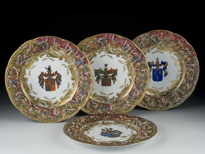 Satz von vier Porzellantellern mit Wappenmalerei und Reliefszenen in der Fahne