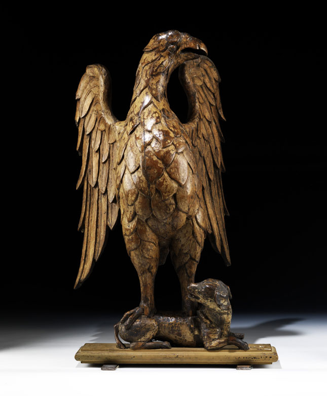 Schnitzfigur eines Adlers, auf dem Rücken eines liegenden Hundes stehend