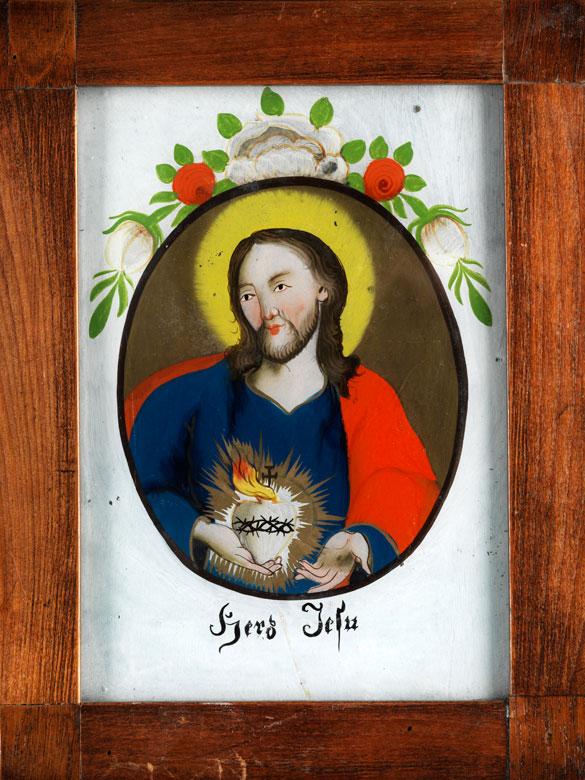 Christusfigur im Oval, auf grauem Grund mit Blütenmalerei.