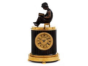 Französische Kaminuhr in Bronze mit bekrönender Figur eines lesenden Kindes
