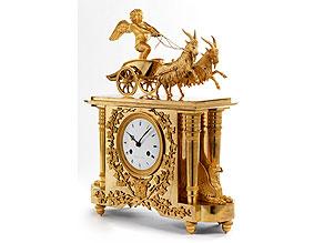 Französische Kaminuhr in feuervergoldeter Bronze mit figürlicher Darstellung eines Amor als Wagenlenker