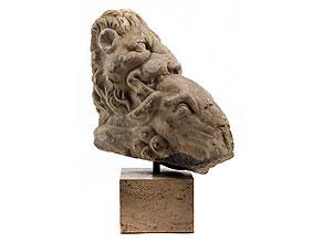 Großes Steinfigurenfragment mit Darstellung eines Löwenkopfes, der ein gehörntes Tier reißt