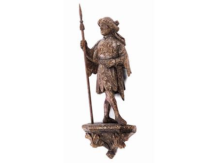 Schnitzfigur eines Mannes mit Lanze und Turban sowie lappig gefranstem Rock