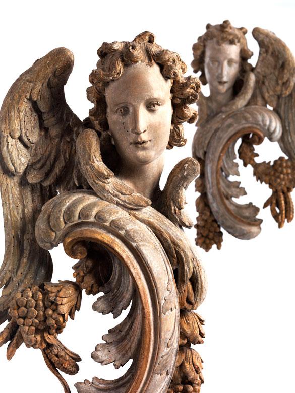 Paar geschnitzte, geflügelte Engelsköpfe an hohen Rocaille-Schnitzereien mit Trauben und Ähren